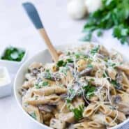 White bowl full of whole wheat penne pasta, chicken, mushrooms, fresh parsley, and parmesan cheese.