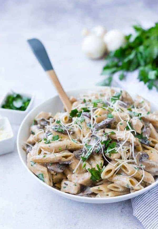 A white bowl full of penne pasta with mushrooms, chicken, parsley, and cheese.