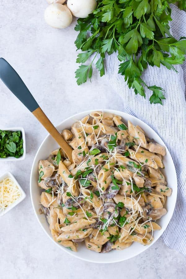 Overhead view of a white bowl filled with penne pasta, mushrooms, chicken, parsley, and parmesan.