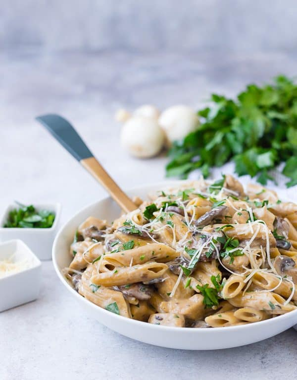 A white bowl filled with whole wheat pasta, mushrooms, and chicken. It is garnished with parsley and cheese.