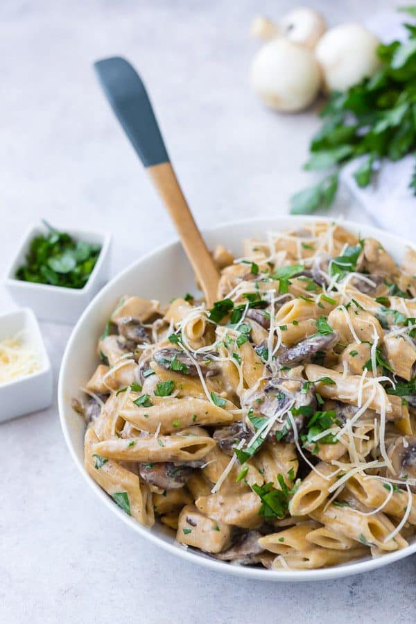Chicken marsala pasta in a creamy sauce in a white bowl with a wooden spoon.