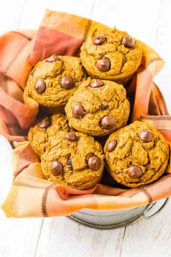 Pumpkin chocolate chip muffins in a basket with orange towel.