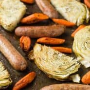 Sausage, cabbage slices, and carrots on a sheet pan, sprinkled with dill.