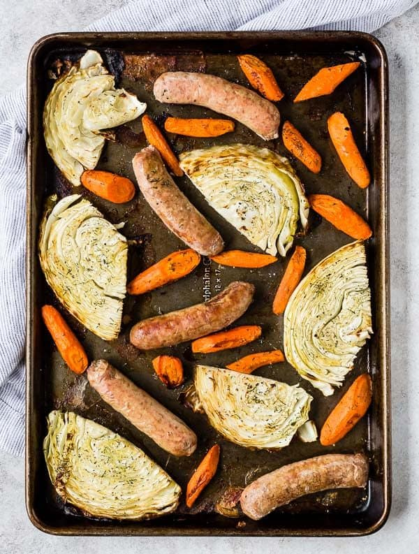 Overhead image of a sheet pan filled with sausages, cabbage slices, and chopped carrots.