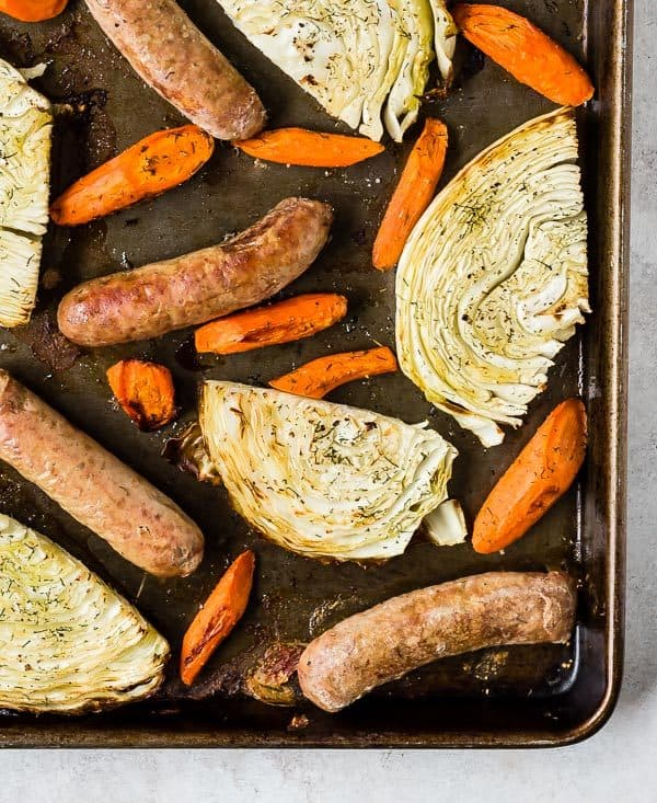 Overhead view of sausages, carrots, and cabbage on a dark gray/brown sheet pan.