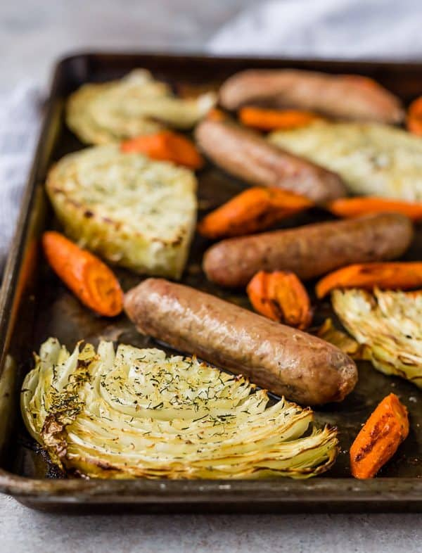 A weathered sheet pan on a gray background, filled with cabbage slices, sausages, and carrots cut on the bias.