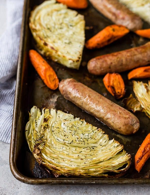 Close up view of a cabbage slice on a sheet pan, surrounded by sausage and carrots.