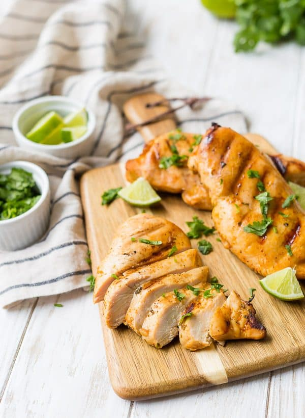 A sliced, grilled chicken breast is on a wooden cutting board with two other chicken breasts. Lime wedges are also pictured.