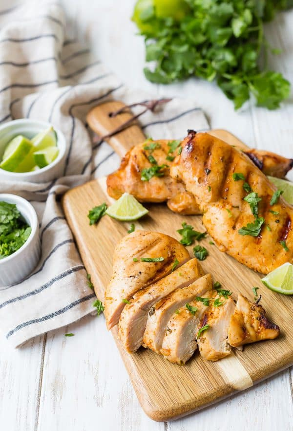 A cutting board with three chicken breasts, one sliced. Lime wedges and fresh cilantro are also pictured.