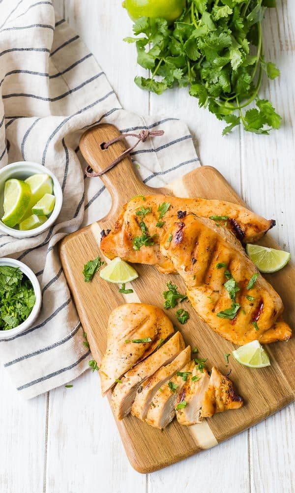 Overhead view of three grilled chicken breasts on a wooden cutting board with a handle. One chicken breast is sliced. All are sprinkled with fresh cilantro.