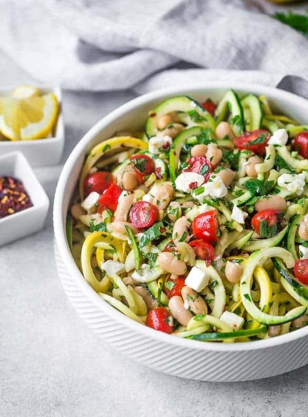 image of zucchini noodle salad in white bowl with tomatoes, feta, and beans