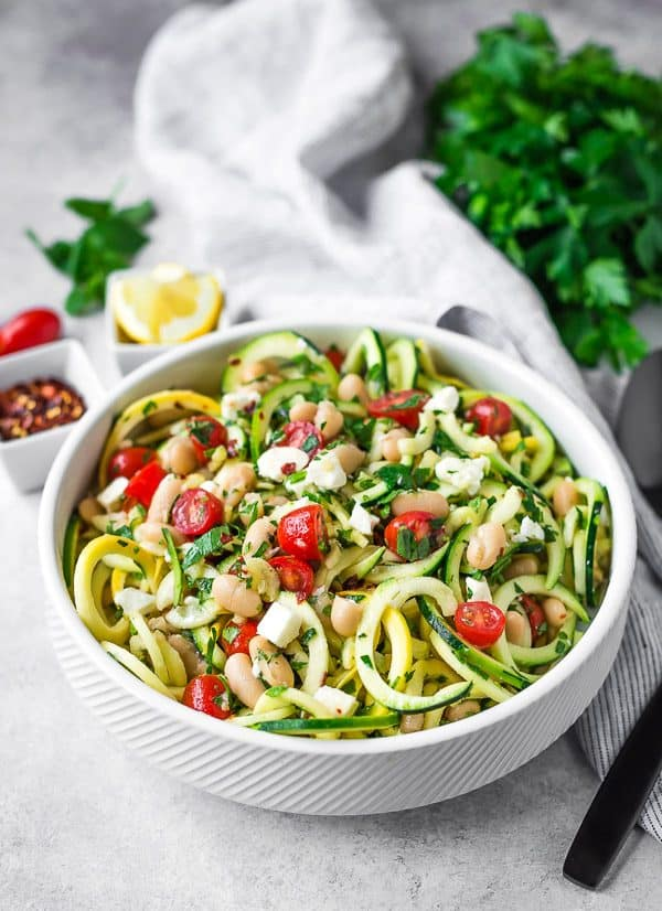 A white bowl full of zucchini and summer squash noodles, feta, great northern beans, tomatoes, and fresh herbs.