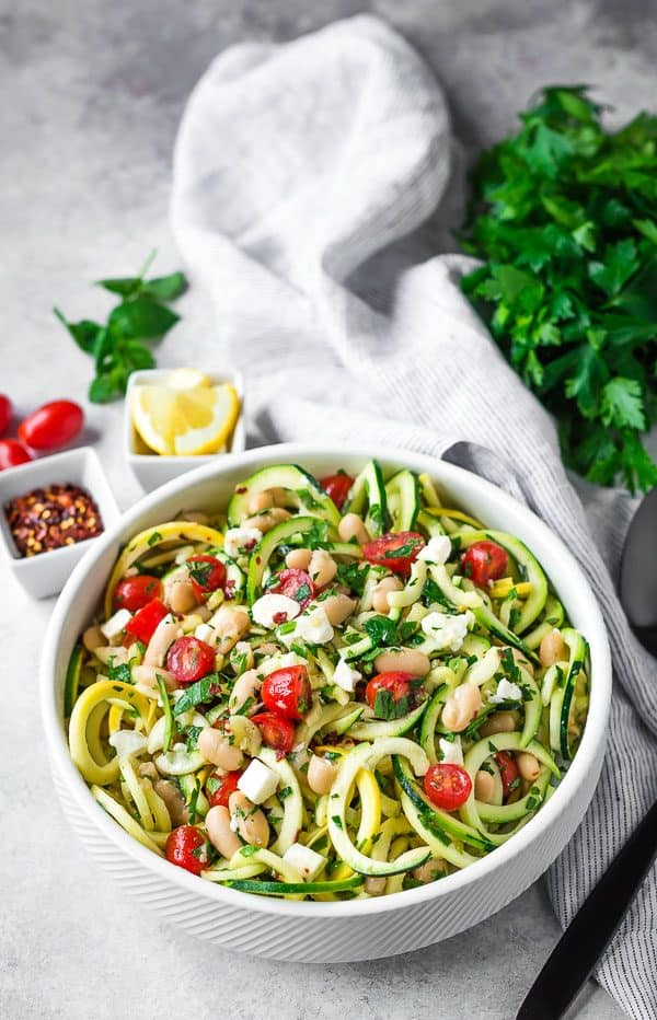Green and yellow squash noodles in a white bowl with diced tomatoes, white beans, feta cheese, and fresh herbs.