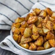Small oval shaped white bowl filled to the brim with roasted potato pieces.