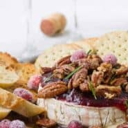 Baked Brie wheel with Cranberries and Candied Pecans with Bourbon. Garnished with sugared cranberries and rosemary.