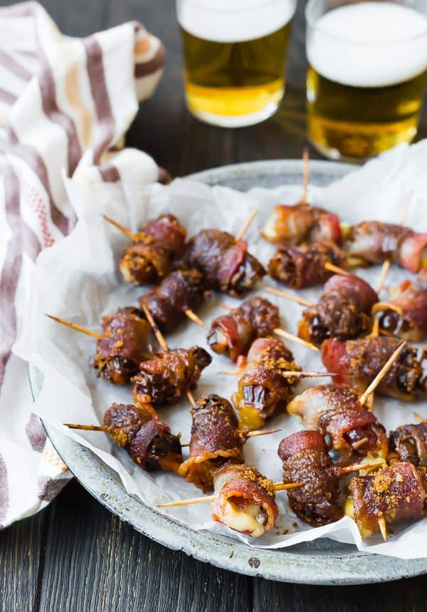 Image of bacon wrapped dates on crinkled parchment paper with two glasses of beer in the background.