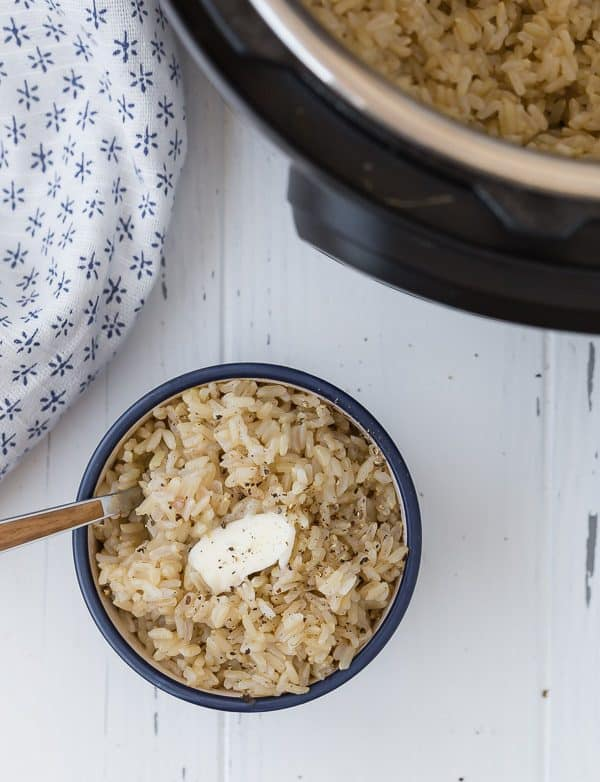Image of Rice in a blue bowl with butter on top and a fork stuck in the bowl. An Instant Pot is in the corner of the image.
