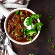 image of texas style chili in a white bowl with a handle, garnished with sour cream, cilantro, and jalapeno