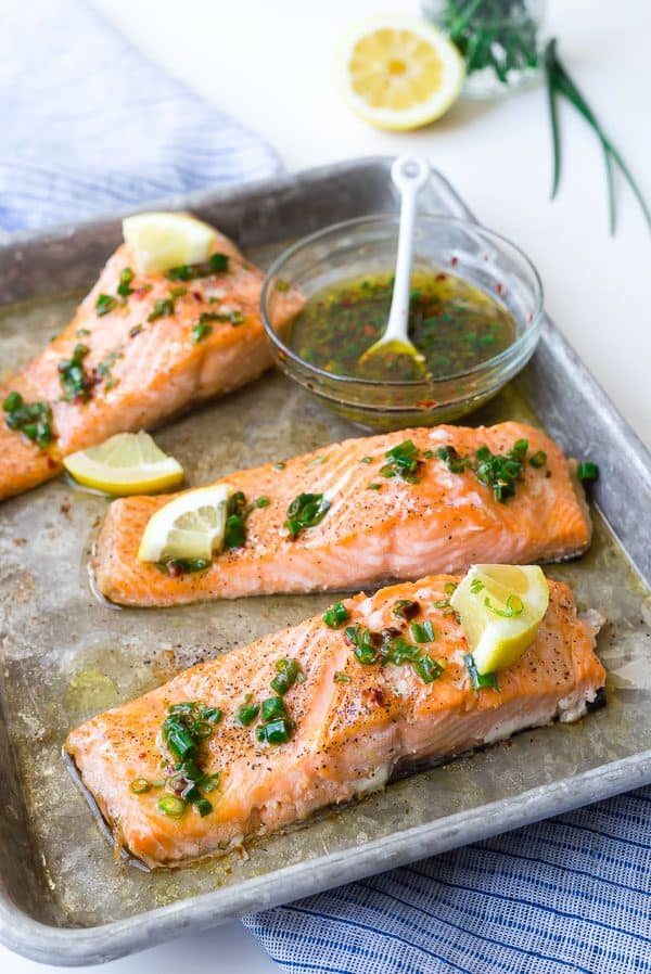 Image of three fillets of easy baked salmon garnished with a lemon chive sauce.