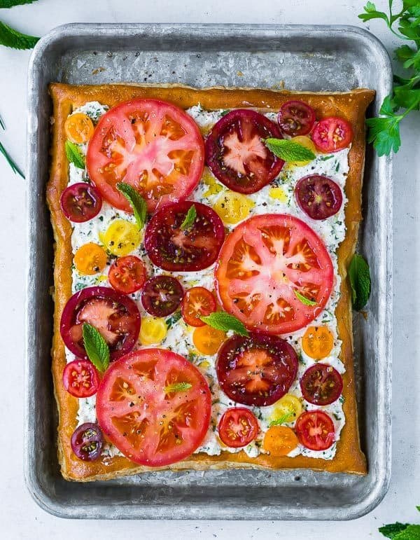 Overhead image of a tomato tart with varied colored tomatoes, fresh mint, and ricotta cheese.