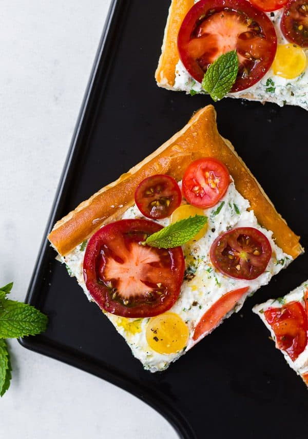 This fresh tomato tart with herbed ricotta tastes like summer on a flaky puff pastry crust. It's easy to make and visually stunning. Make it for your next party!