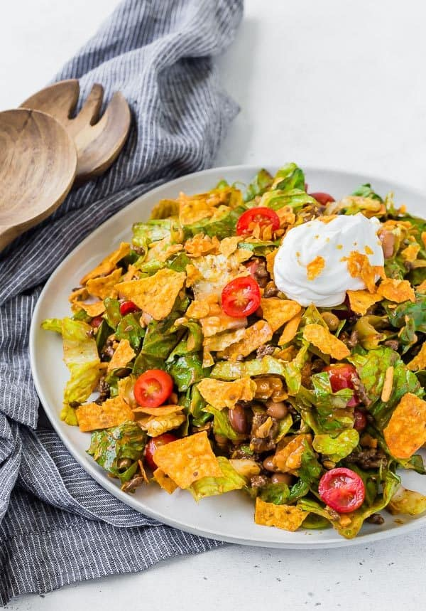 image of classic taco salad on a plate, garnished with sour cream