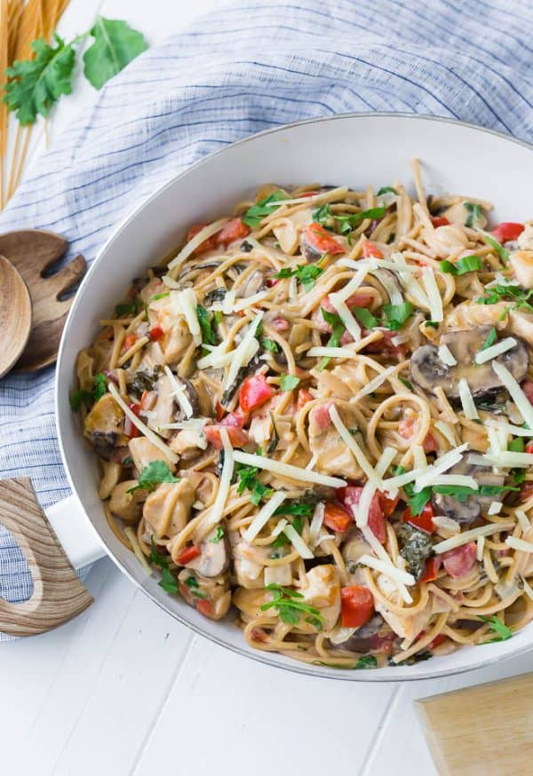 Image of one pan creamy chicken spaghetti garnished with parsley and extra cheese.