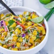 image of bright and colorful mango slaw, the perfect slaw for fish tacos, in a white bowl with a black spoon. Garnished with a lime.