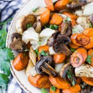 Balsamic roasted vegetables in a bowl, garnished with fresh flat leaf parsley.