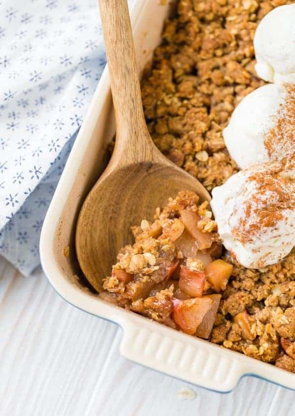 Close up image of apple crisp with ginger, an easy recipe that's perfect for fall. Ice cream with cinnamon is on top.