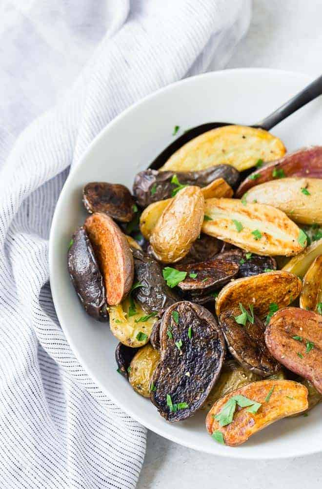Image of beautiful colorful fingerling potatoes in a white bowl with a black spoon.