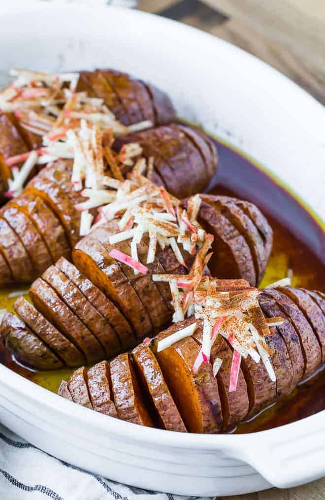 Image of four hasselback sweet potatoes in a white baking dish, topped with apples.