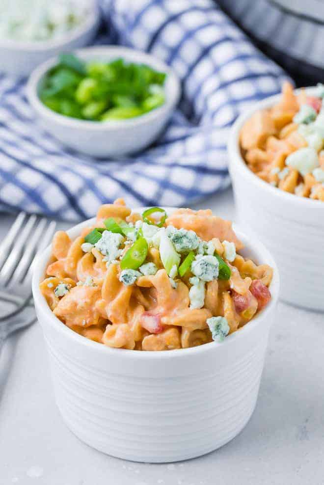 Image of a bowl of instant pot buffalo chicken pasta garnished with green onions and blue cheese.