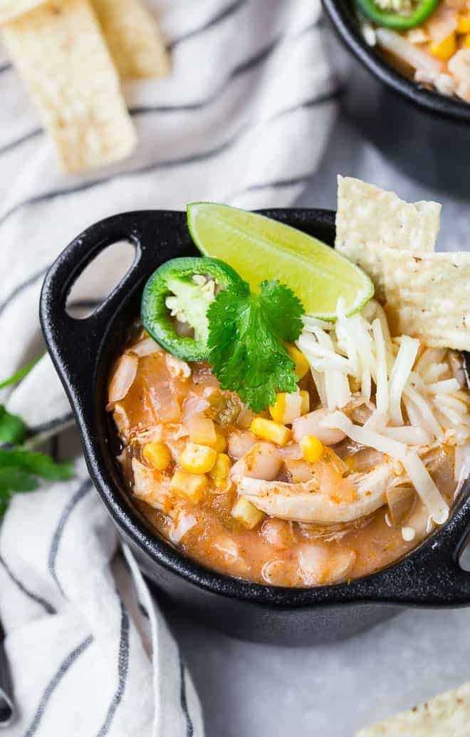 Image of pressure cooker white chili in a black bowl with garnishes.