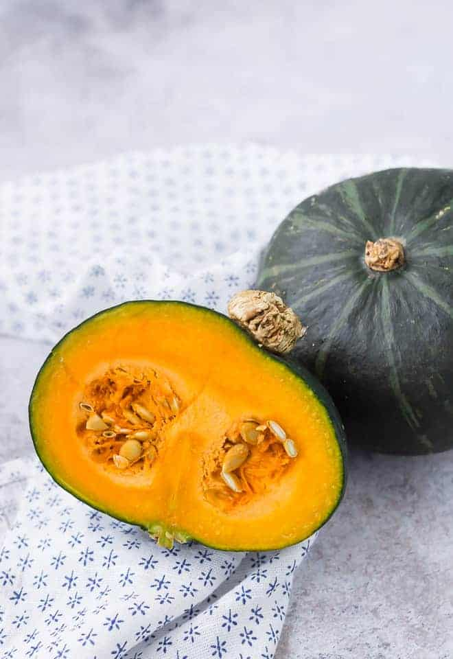 Image of a whole kabocha squash and a half kabocha squash with the seeds still present.