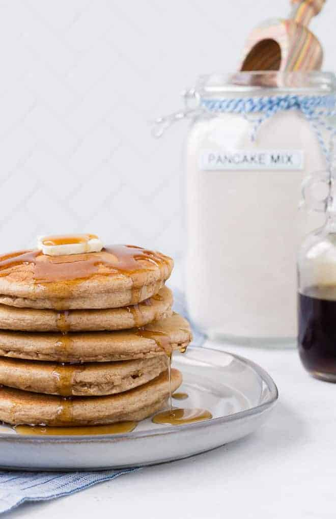 Image of a stack of pancakes with homemade pancake mix in the background.