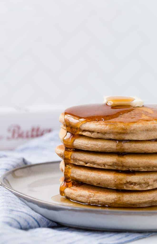 image of a beautiful stack of whole wheat pancakes with butter and maple syrup.