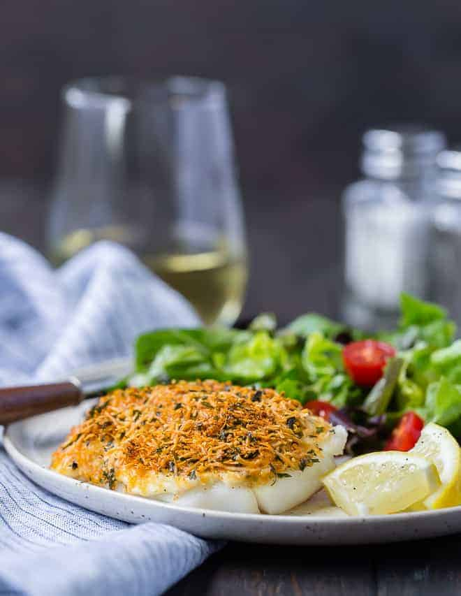 Image of baked parmesan cod with a glass of wine in the background.