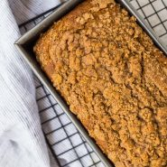 Image of pumpkin streusel bread, shot from above, bread is still in loaf pan on cooling rack.