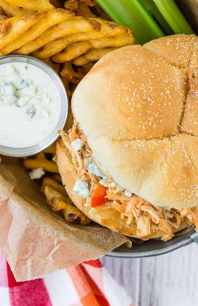 Slow cooker buffalo chicken on a soft white bun.