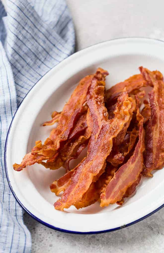 Image of baked bacon on a white platter.