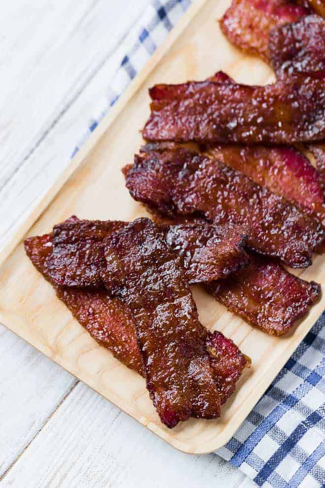 Image of candied bacon on a wooden serving plate.