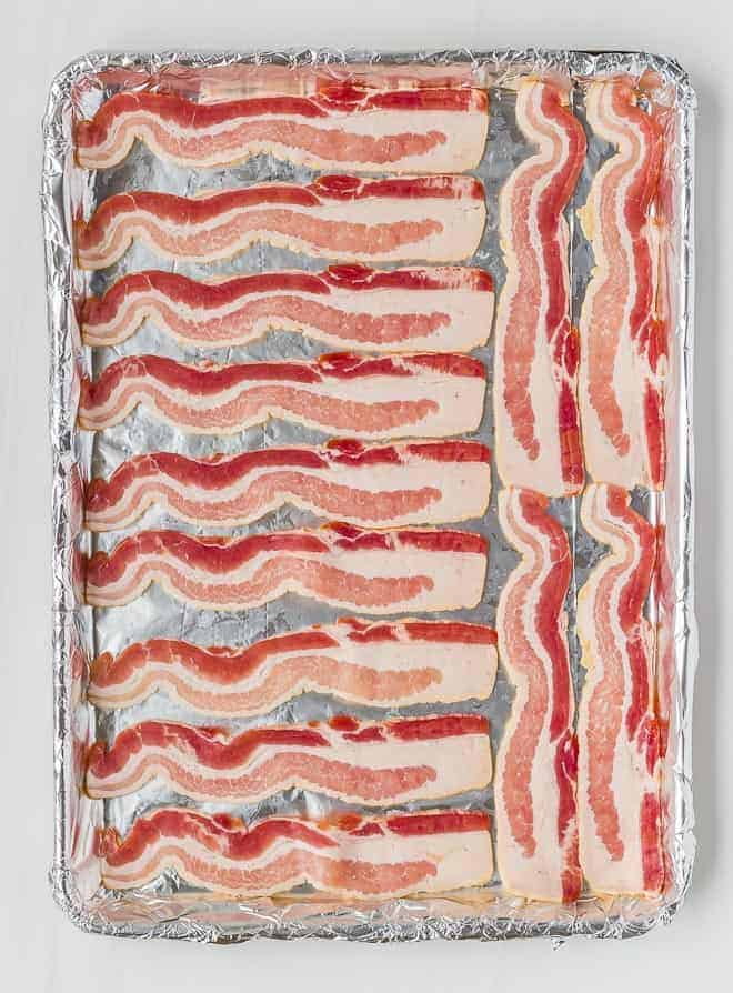 Image of raw bacon on a sheet pan
