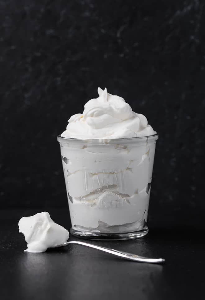 Image of freshly whipped whipped cream in a glass. A spoonful of whipped cream sits on the surface next to it. Photograph taken on a black background.