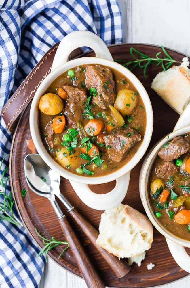 Photograph of a bowl of hearty beef stew that's been made in a crockpot. Two bowls are pictured, along with two spoons and a few pieces of bread.
