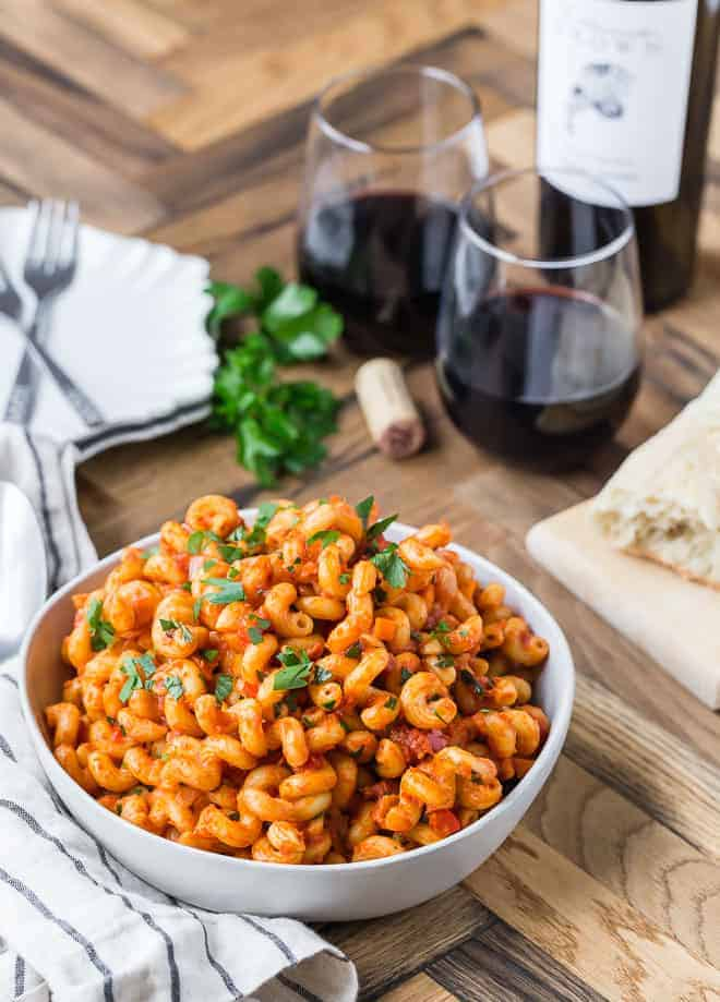 Pancetta pasta in a white bowl with red wine in the background.