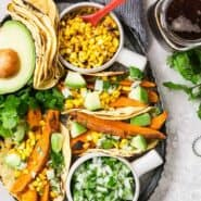 Image of vegan sweet potato tacos on a platter with charred corn, onions and cilantro, and avocado. A glass of beer sits next to the platter.