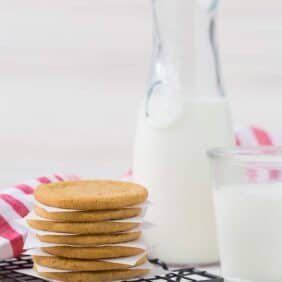 Image of a stack of windmill cookies in front of a carafe of milk. Whole spices (nutmeg, cinnamon, and cloves) pictured in the foreground.