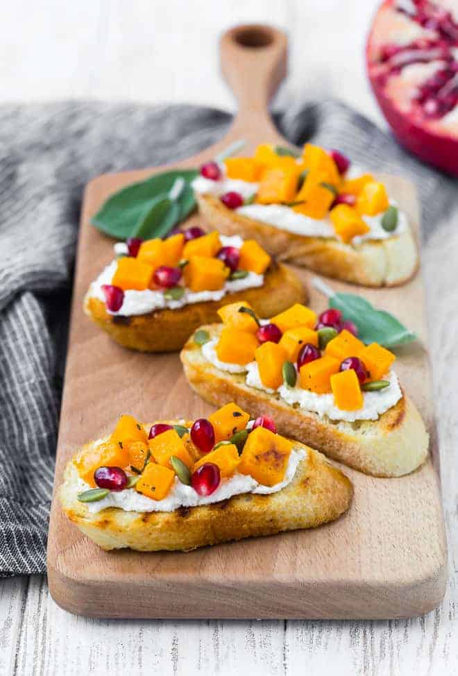 Crostini with squash, pomegranate, ricotta, and pepitas.