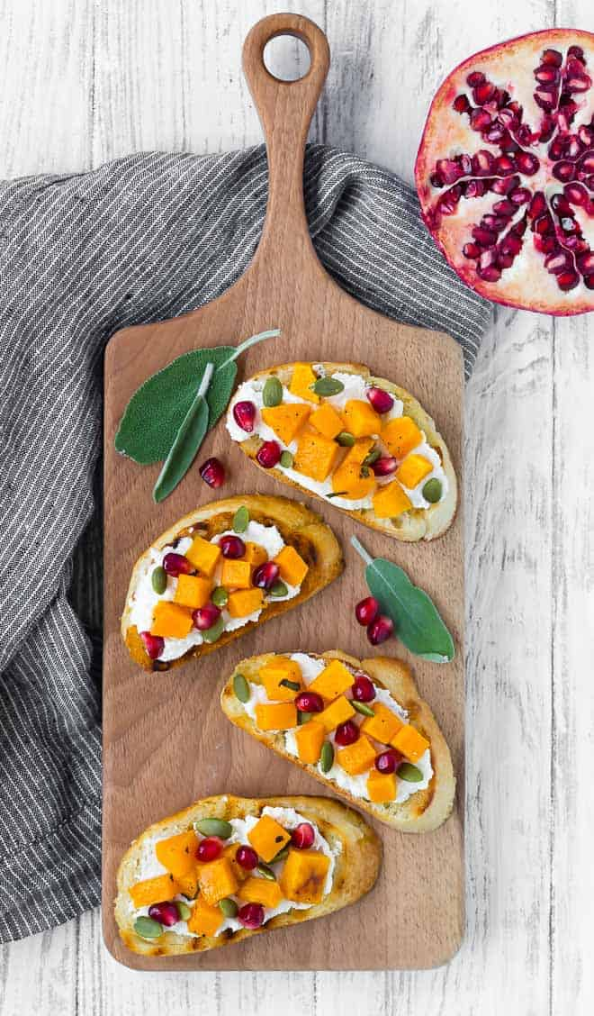 Photo of four squash crostini arranged on a wooden platter.